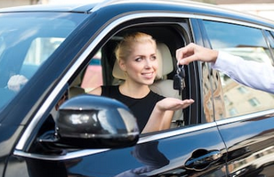 Young_woman_getting_keys_from_a_car_rental
